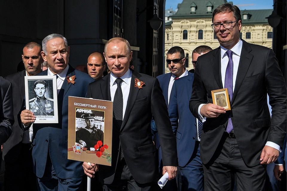 На фото слева премьер-министр Израиля Биньямин Нетаньяху, президент России Владимир Путин с портретом своего отца-фронтовика и президент Сербии Александр Вучич во время акции «Бессмертный полк»